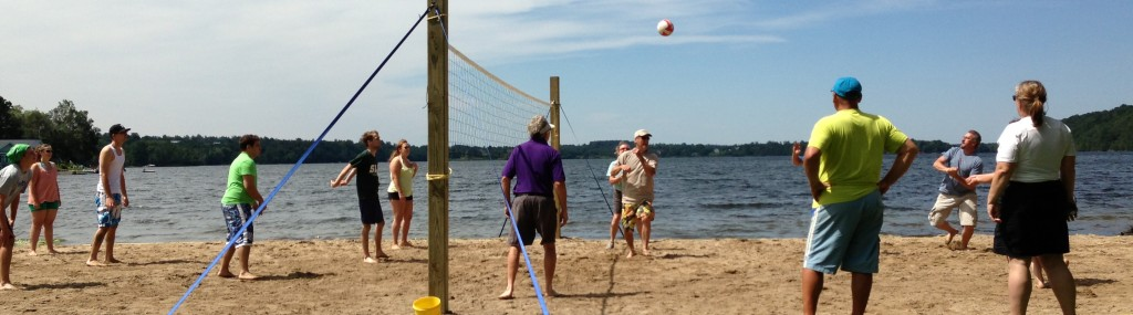 A group of people playing beach volleyball